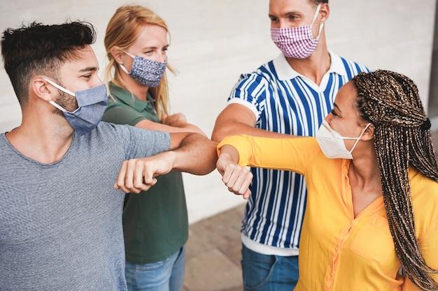 Vrienden van jonge mensen stoten hun ellebogen in plaats van te begroeten met een knuffel