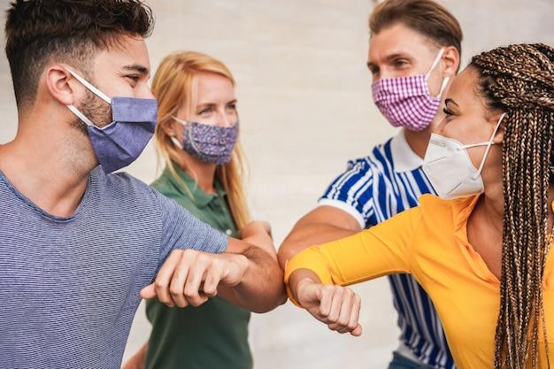 Vrienden van jongeren stoten hun ellebogen in plaats van te begroeten met een knuffeloog