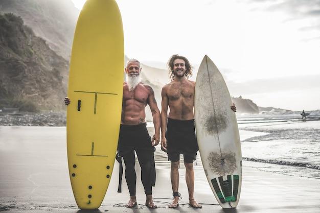Vrienden van meerdere generaties die op tropisch strand gaan surfen