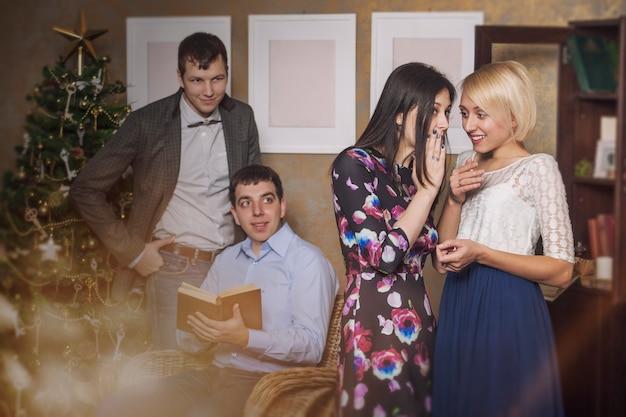 Vrienden van vier mannen en vrouwen die gaan fluisteren in het kerstinterieur