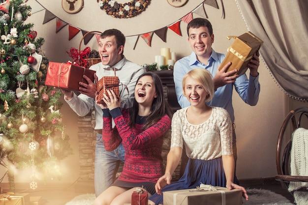 Vrienden van vier mannen en vrouwen geven cadeautjes onder de boom in het kerstinterieur