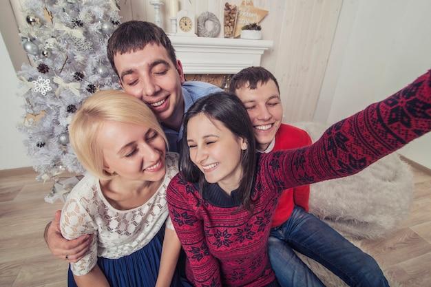 Vrienden van vier mannen en vrouwen maken het zelfportret op mobiel in kerststijl