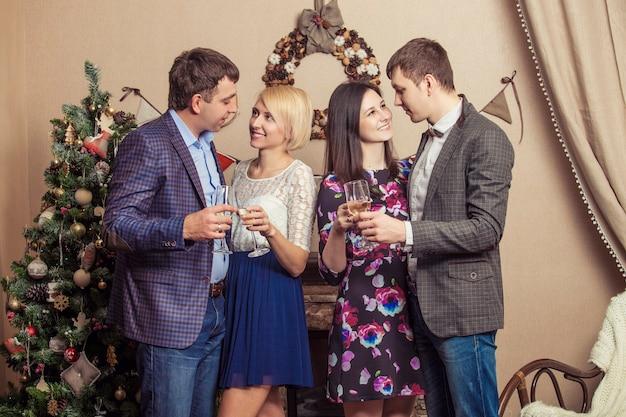 Vrienden van vier mannen en vrouwen met bacale vieren feest met champagne in het kerstinterieur