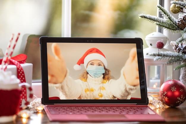 Vrienden vieren kerstvakantie online door videochat in quarantaine. lockdown blijf thuis concept. kerstfamiliefeest tijdens pandemie coronavirus covid 19
