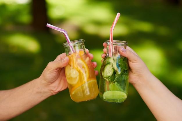 Vrienden vieren met detox sap cocktails op groene natuur achtergrond