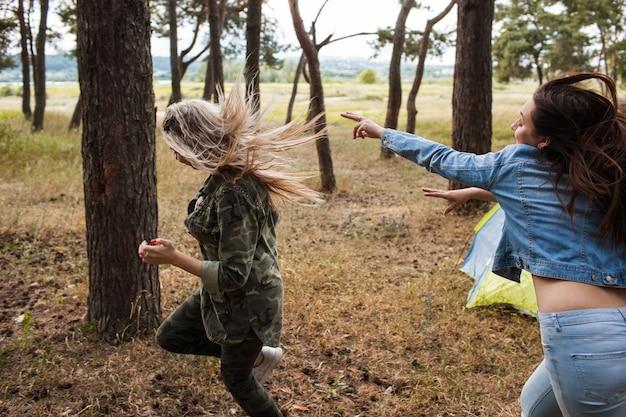 Vrienden vrouwen groep lopende competitie concept. sport achtervolgingsspel op de natuur.