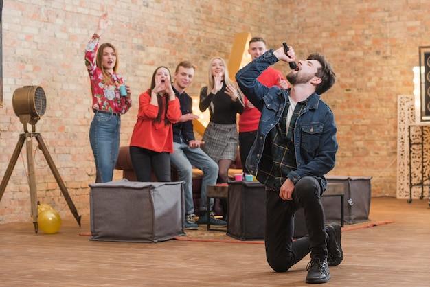Vrienden zingen karaoke op een feestje