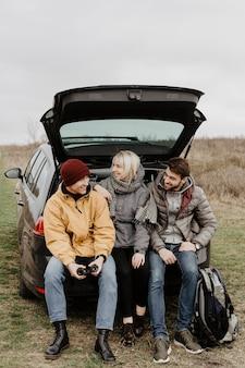 Vrienden zitten aan de achterkant van de auto