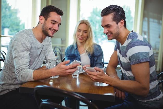 Vrienden zitten aan tafel en met behulp van de mobiele telefoon in cafã ©
