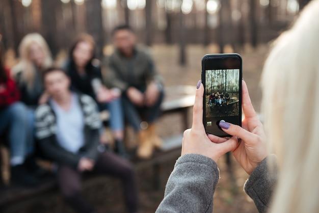 Vrienden zitten buiten in het bos. focus op telefoon.
