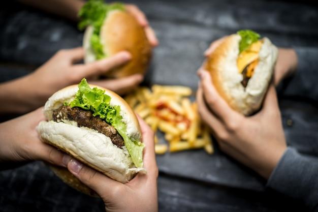 Vrienden zitten en hamburger eten