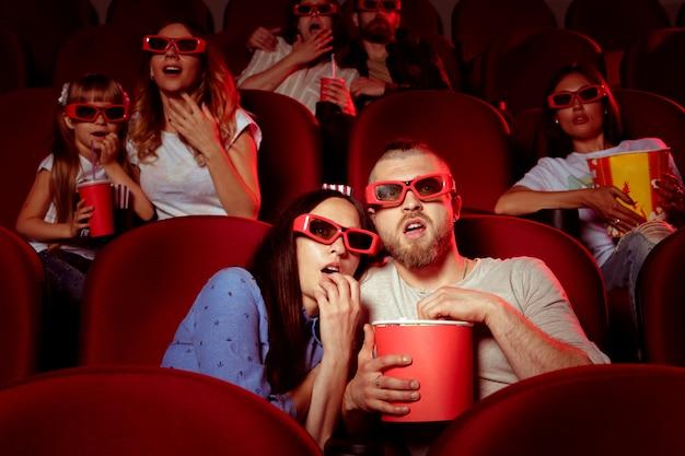 Vrienden zitten in bioscoop kijken film eten popcorn en drinkwater.