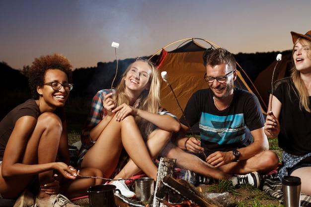 Vrienden zitten in de buurt van vreugdevuur, glimlachen, gitaar spelen camping grill marshmallow.