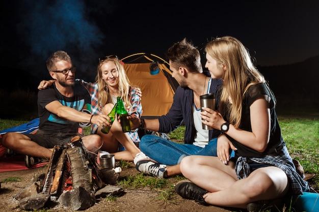 Vrienden zitten in de buurt van vreugdevuur, glimlachen, spreken, rusten, drinken beer