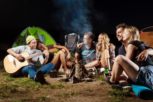 Vrienden zitten in de buurt van vreugdevuur, glimlachen, spreken, rusten, gitaar spelen