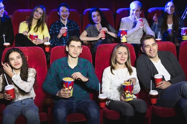 Vrienden zitten in een bioscoop en kijken naar film die popcorn eten