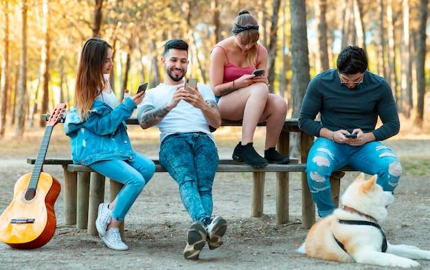 Vrienden zitten in een park, iedereen gebruikt smarptohne