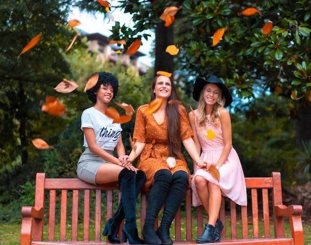 Vrienden zitten in het park in de herfst, een blonde, een brunette en een latijns meisje met afrohaar