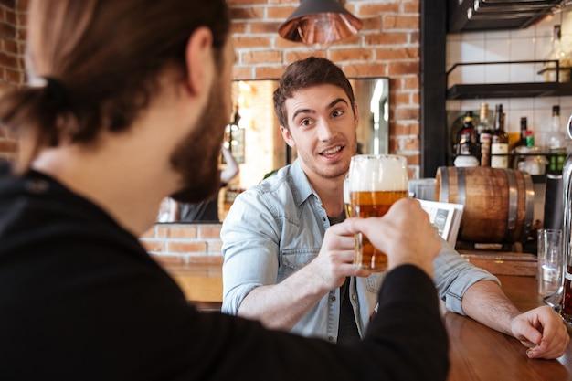 Vrienden zitten op bar en drinken