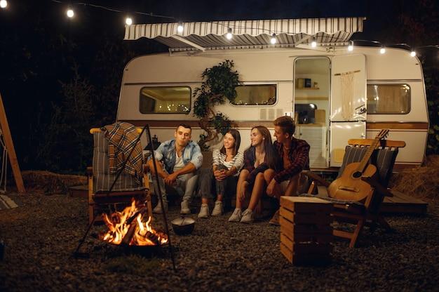 Vrienden zitten 's nachts bij het kampvuur, picknicken op kamperen in het bos