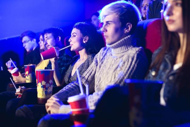 Vrienden zitten samen en eten popcorn terwijl ze films kijken in een bioscoop