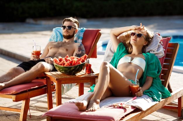 Vrienden zonnebaden, cocktails drinken, liggend op ligstoelen bij het zwembad