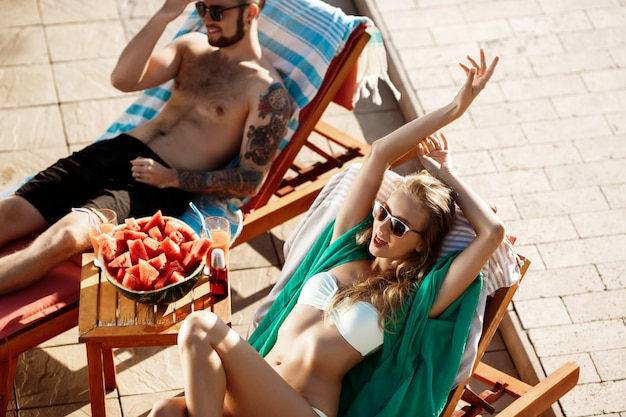 Vrienden zonnebaden, glimlachen, liggend op ligstoelen bij zwembad