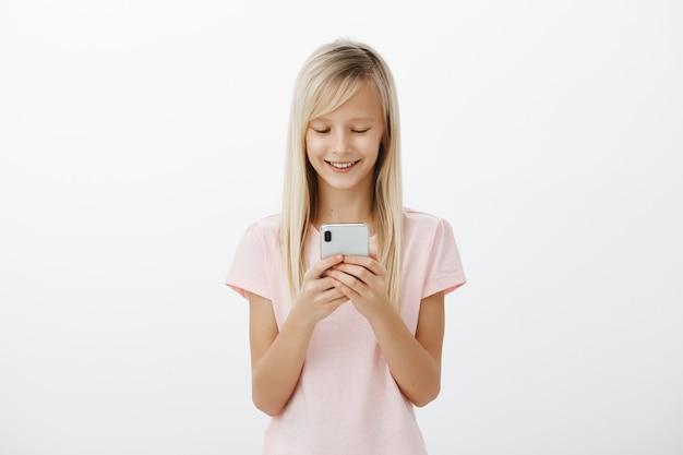 Vrienden zullen jaloers zijn als ze mijn nieuwe telefoon zien. tevreden, vrolijk schattig kind met blond haar in roze t-shirt, smartphone vasthouden, lachen, scherm kijken, grappige animatie kijken over grijze muur