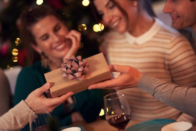 Vriendengroep die kerstcadeautjes thuis uitwisselt