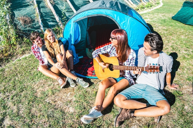 Vriendengroep plezier buiten zingen op picknickkamp met vintage gitaar