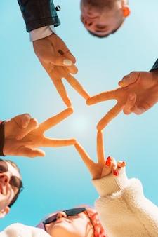 Vriendenhanden die samen met vredesgebaar samenbrengen