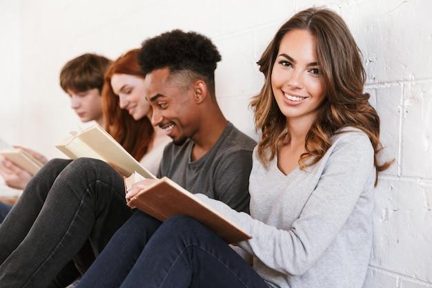Vriendenstudenten die over witte muur zitten. focus op vrolijke vrouw.