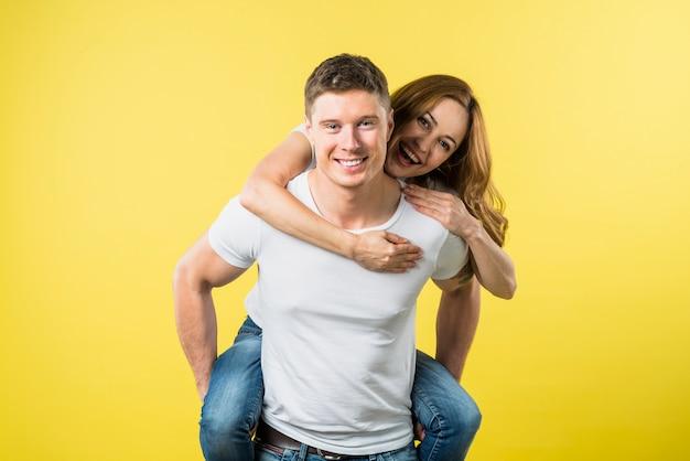 Vriendin die geniet van de rit op de rug van haar vriendje op haar vriendje