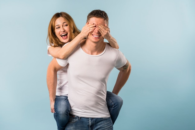 Vriendin die van de rit op een aan de rug op haar vriend tegen blauwe achtergrond genieten