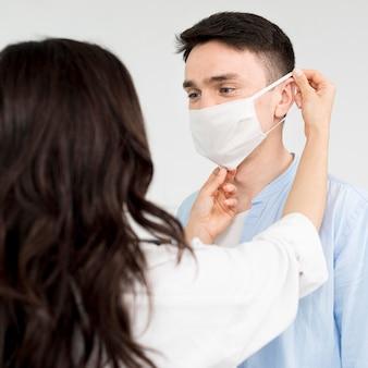 Vriendin die vriend helpt gezichtsmasker op te zetten