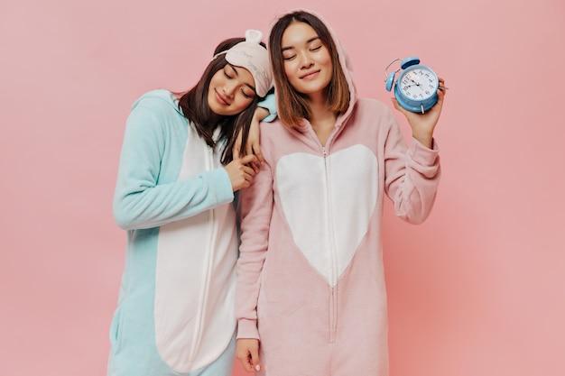 Vriendin in pyjama pose met gesloten ogen op roze muur