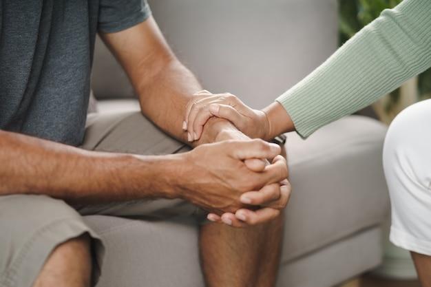 Vriendin of familie zit en houdt elkaars hand vast tijdens het opvrolijken van de mentaal depressieve man, psycholoog biedt mentale hulp aan de patiënt. ptss geestelijke gezondheidsconcept