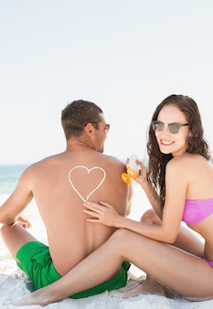 Vriendin zonnebrandcrème toe te passen op vriendje