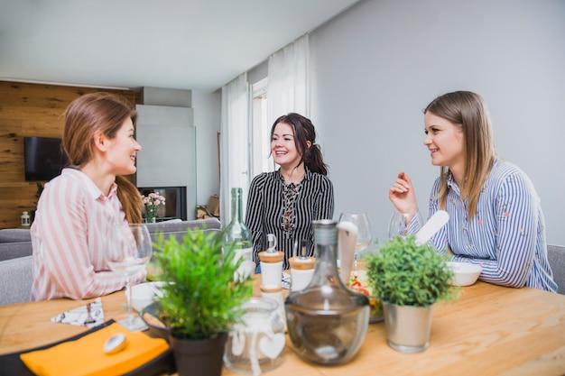 Vriendinnen aan tafel lachen en praten