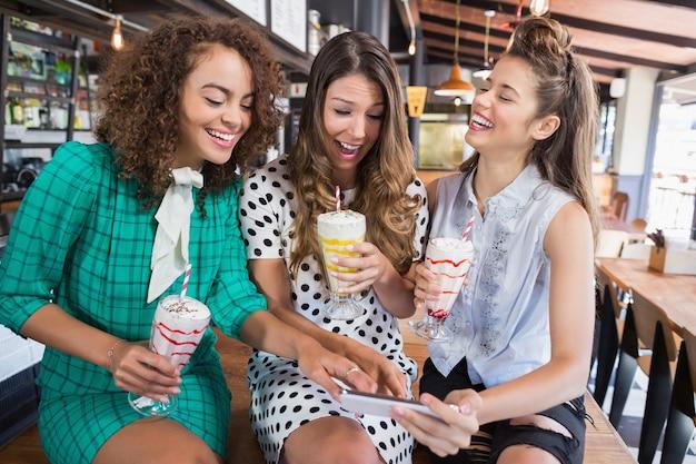 Vriendinnen bespreken via mobiele telefoon zittend in restaurant