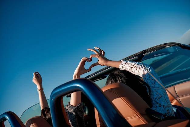 Vriendinnen cabriolet rijden met de handen omhoog en plezier hebben