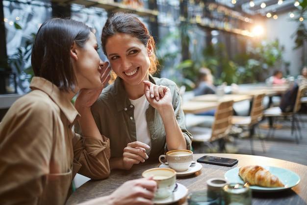 Vriendinnen chatten in cafe