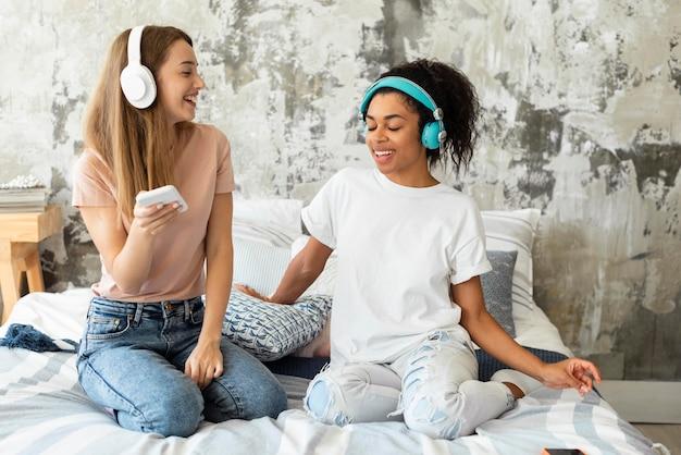 Vriendinnen dansen samen op bed thuis