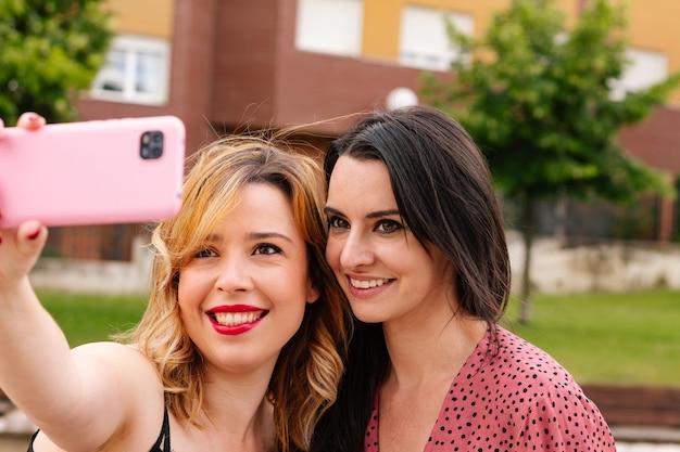 Vriendinnen die buiten een foto maken met hun roze smartphone.