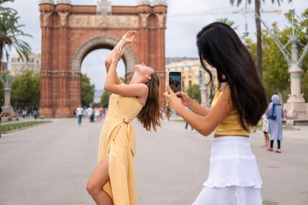 Vriendinnen die foto's maken in de buurt van een stedelijke attractie