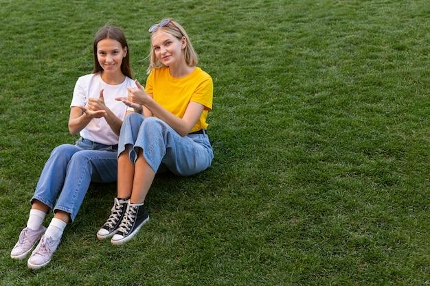 Vriendinnen die gebarentaal buiten gebruiken met kopie ruimte