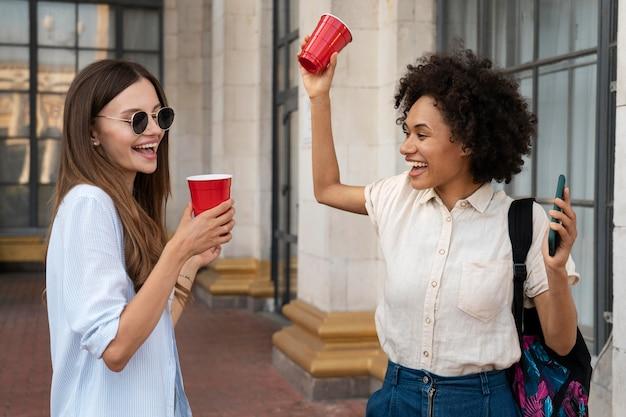 Vriendinnen die samen plezier hebben buiten met plastic bekers