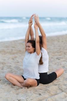 Vriendinnen doen yoga op het strand