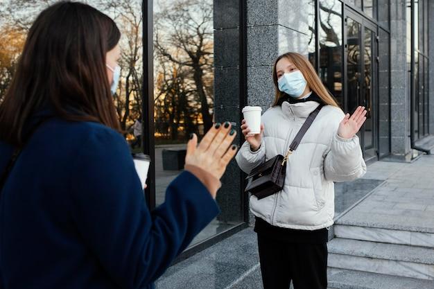 Vriendinnen dragen maskers en zwaaien