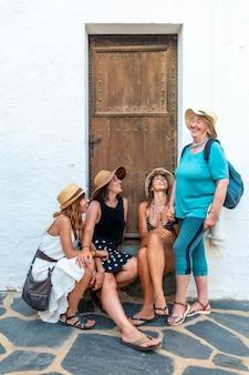 Vriendinnen en een oude vrouw die in de zomer van de vakantie genieten. twee zussen met haar moeder en een vriend zitten lachend op de mediterrane vakantie. spanje